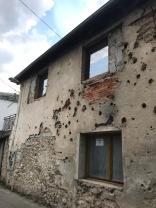 Dinding dengan sisa lubang peluru